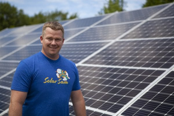 Solar Sam Founder and CEO Ches Heitmeyer with Solar Panel Array Installation Behind. Servicing both Missouri Illinois Solar Panel Needs